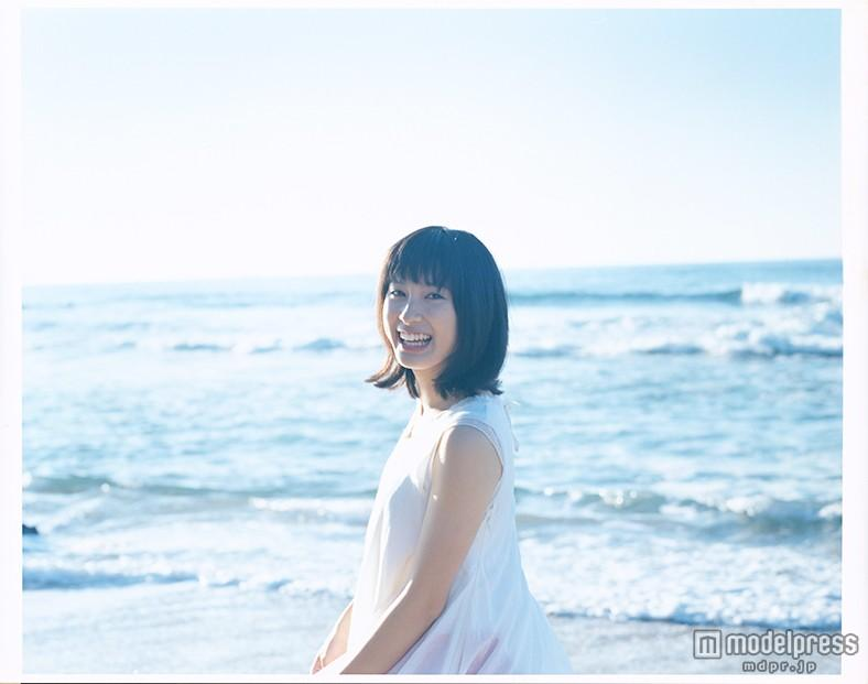 寄せては返す波を背景に極上の笑顔で笑う土屋太鳳