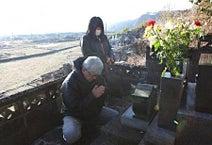 ◎墓前で冥福を祈る家族=岩手